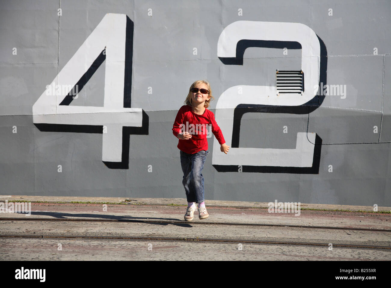 Young happy girl running at camera with big naval numbers '42' in background - Stock Image
