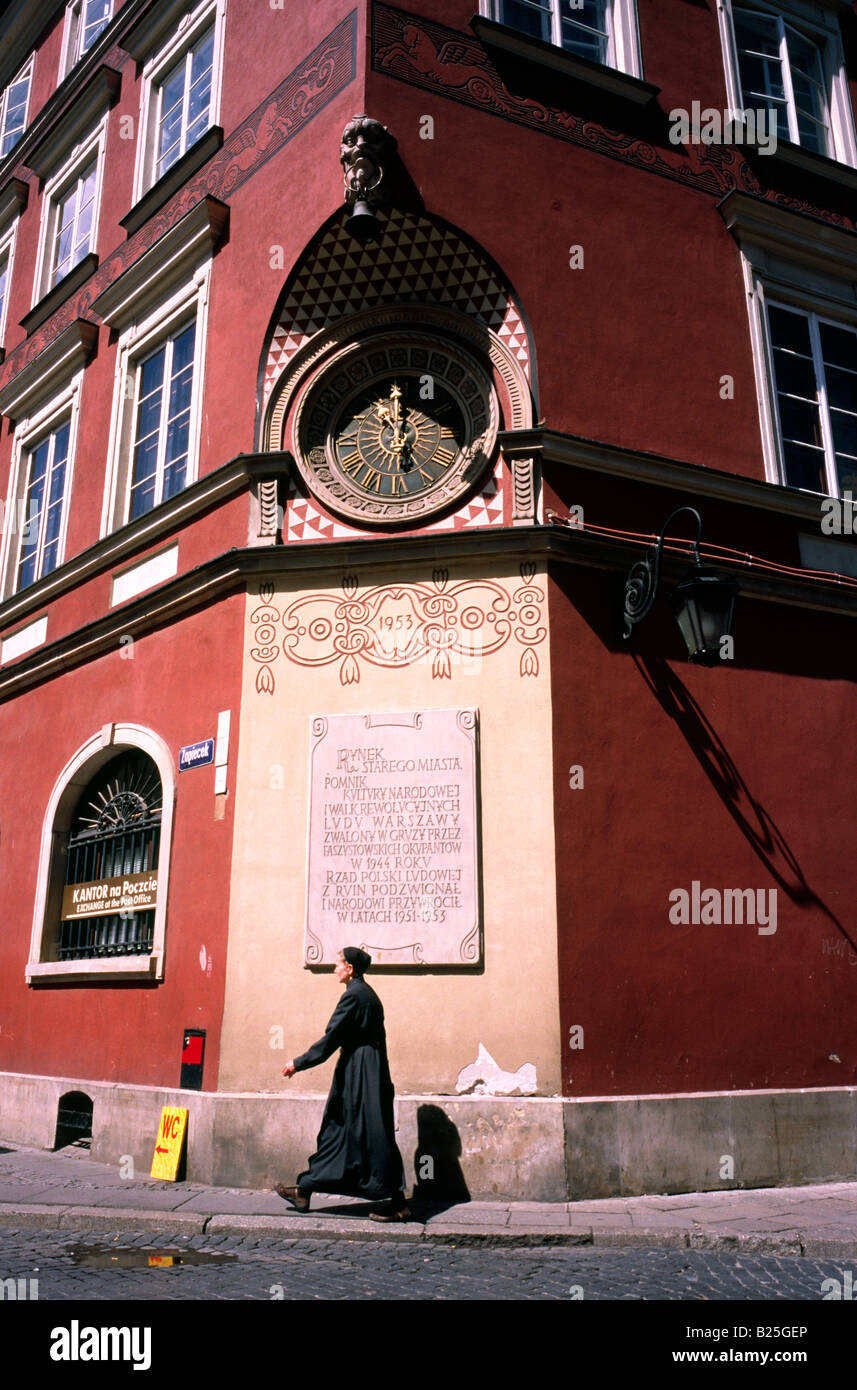 July 8, 2008 - Nun walking past a clock in the Stare Miasto, the Old Town of the Polish capital of Warsaw. - Stock Image