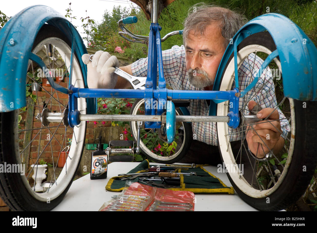 A man repairing a childs tricycle in his back garden - Stock Image