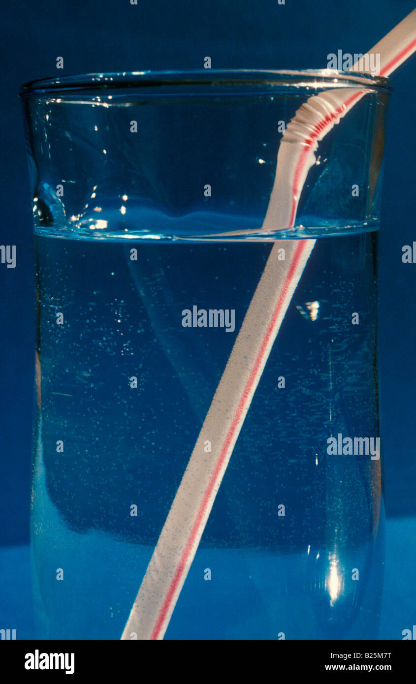 Light refraction glass of water and straw - Stock Image