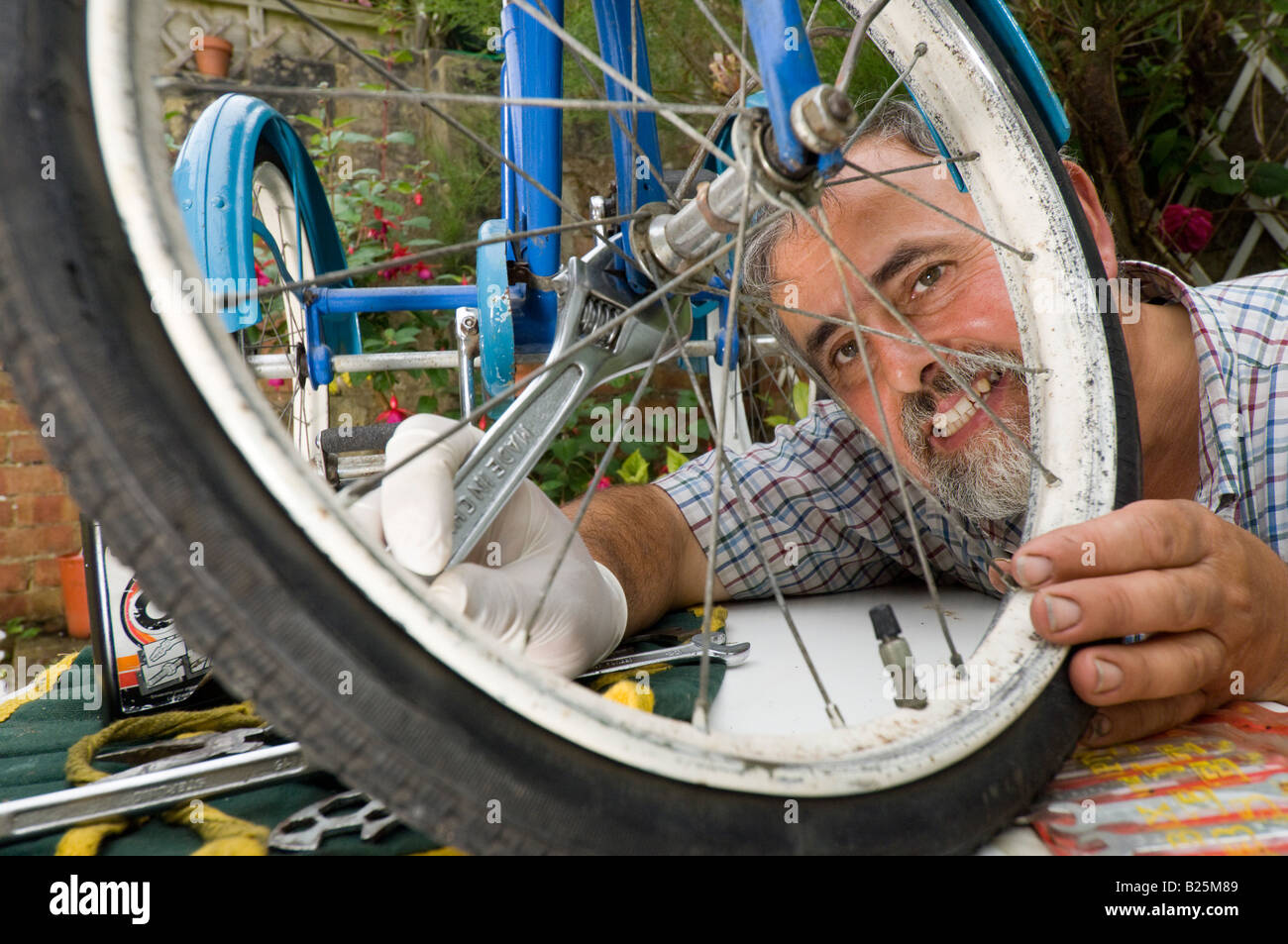 A man repairing a childs tricycle - Stock Image