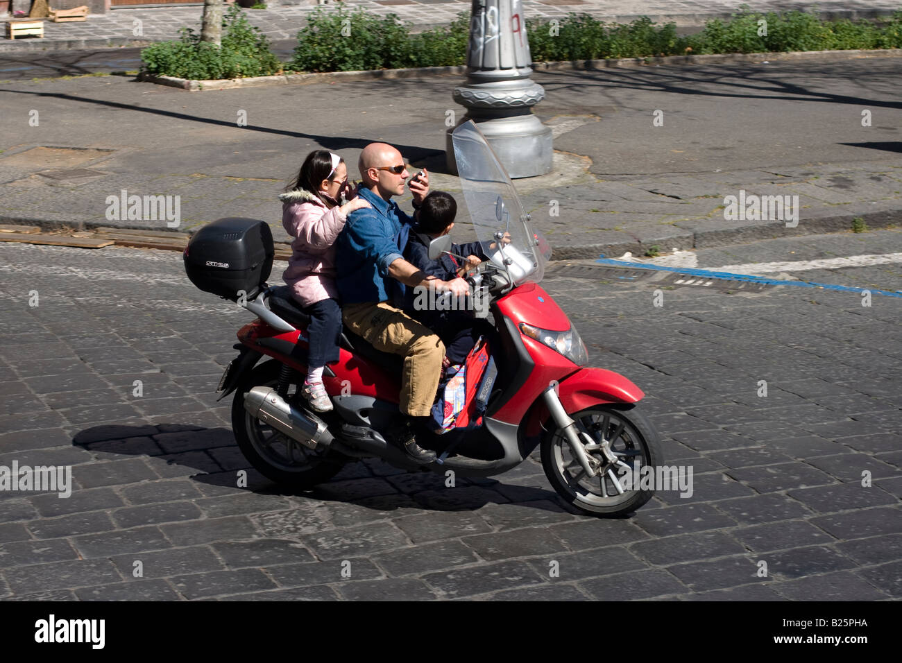 Man rides motorbike with his children and talks on mobile phone in Catania, Sicily, Italy - Stock Image