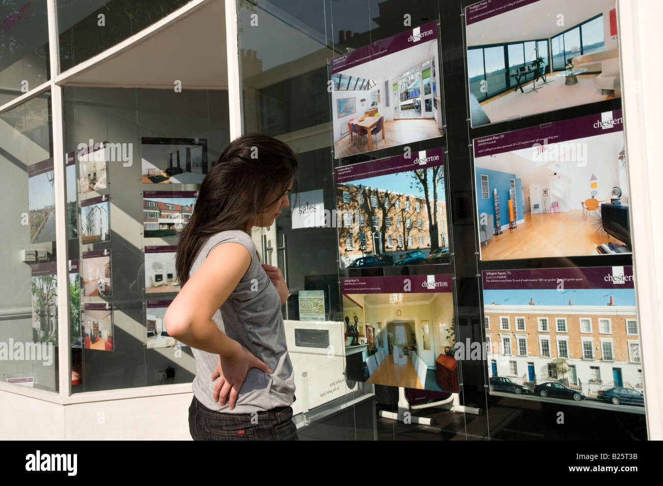 Young first time buyer looking at expensive houses for sale in young first time buyer looking at expensive houses for sale in estate agent window in london england uk sisterspd