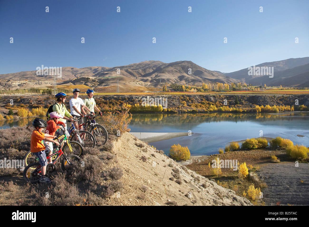 Mountain Bikers Lake Dunstan and Autumn Colours Bannockburn Central Otago South Island New Zealand Stock Photo