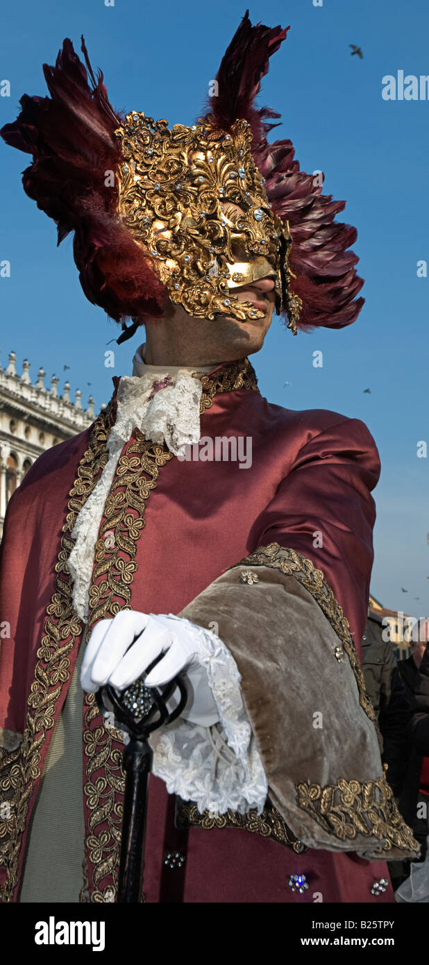 Carnival Venetian disguise wearing a golden mask with gems and plumes. Venice Italy Europe - Stock Image