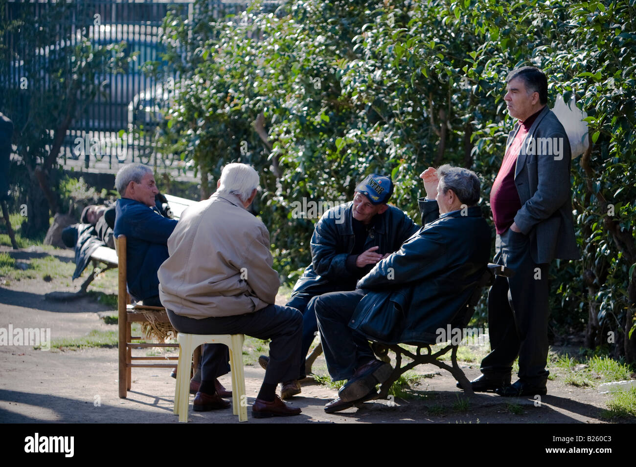 Elderly people talk in a park in Catania, Sicily, Italy - Stock Image
