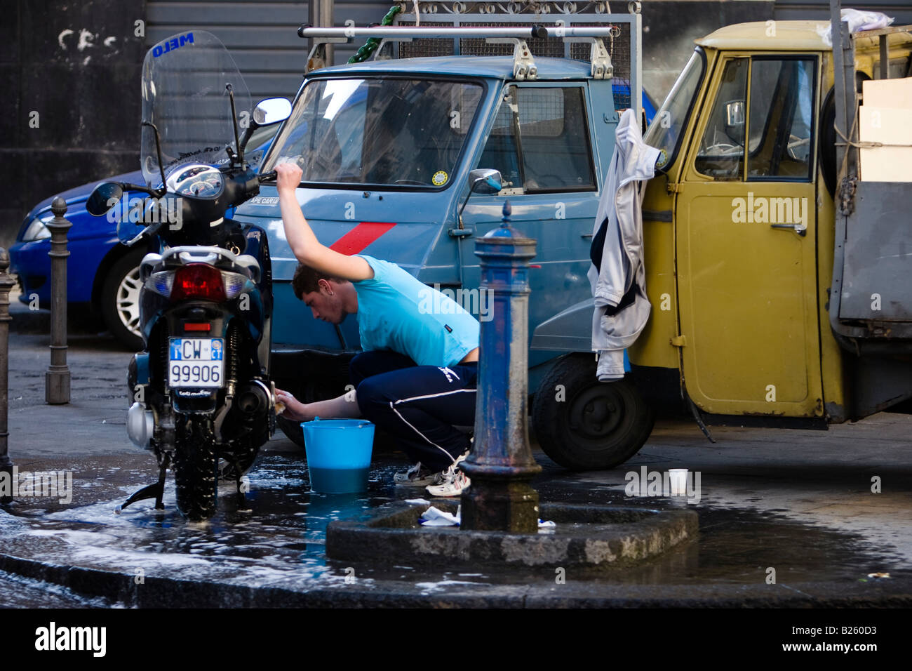Young man washes a motorbike on a street in Catania, Sicily, Italy - Stock Image