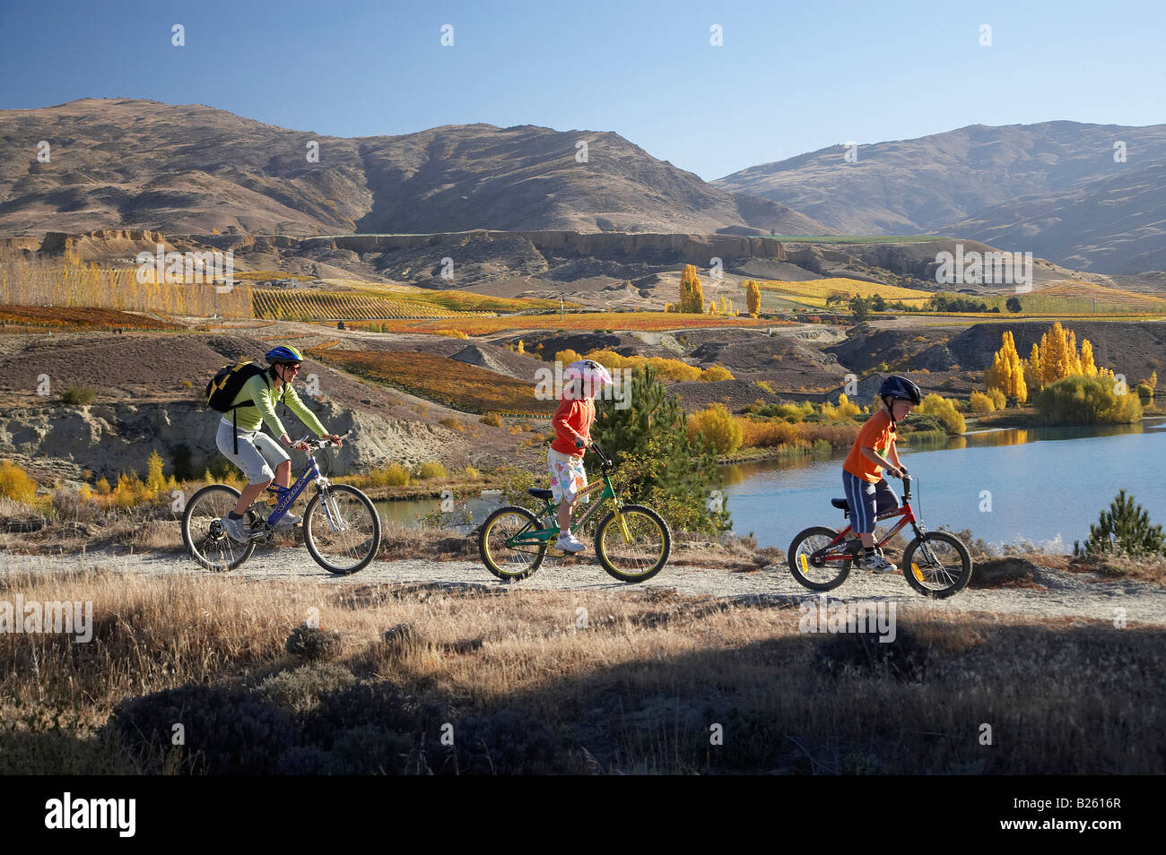 Mountain Bikers Lake Dunstan and Autumn Colours Bannockburn Central Otago South Island New Zealand Stock Photo