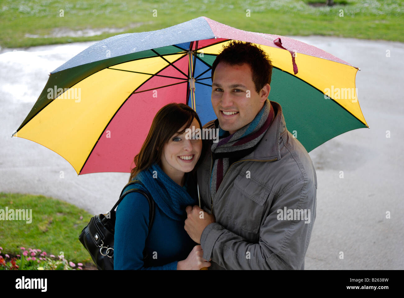 A happy young couple shelter form the rain under a large umbrella - Stock Image