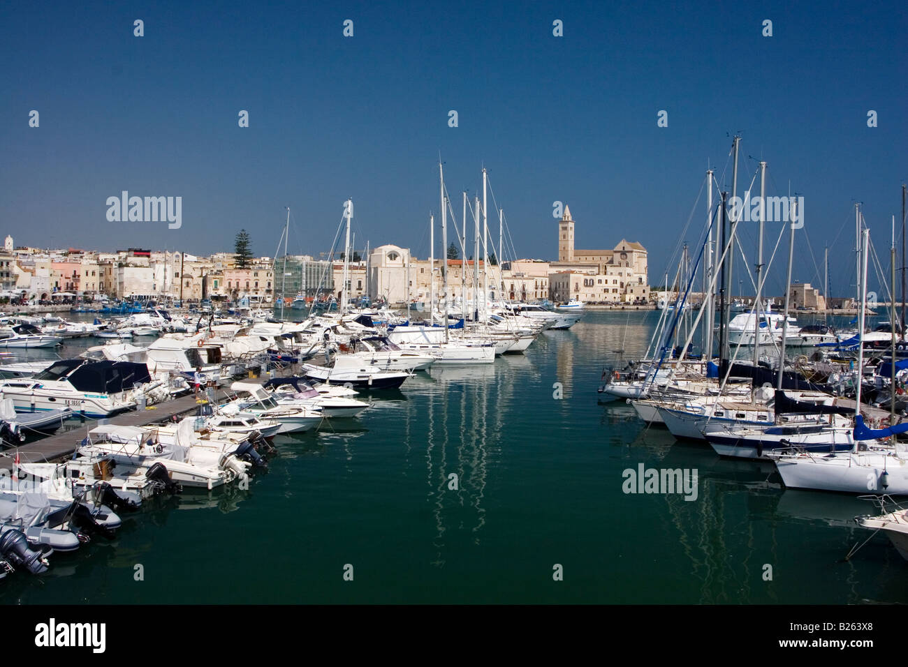 Boats are moored in the marina in front of the cathedral in Trani, Italy. - Stock Image