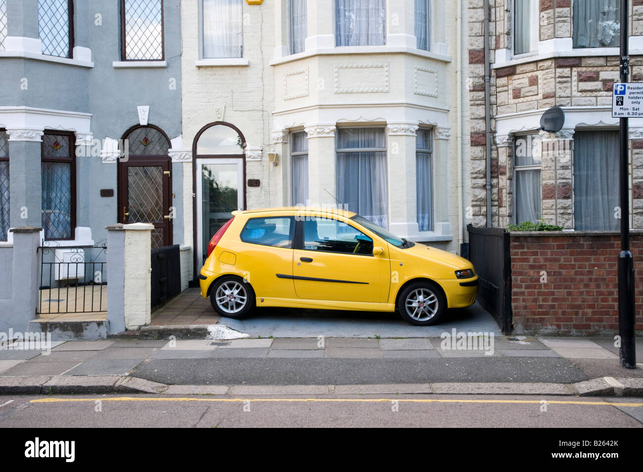 Car parked in front garden of terraced house, London, England, UK - Stock Image