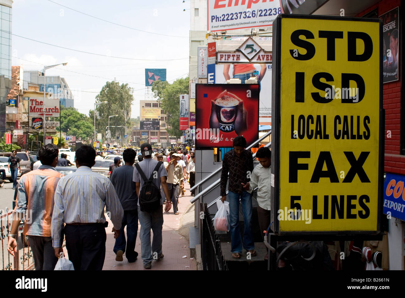 A busy street in Bangalore. People walk on Brigade Road while a sign advertises public telephone facilities. - Stock Image