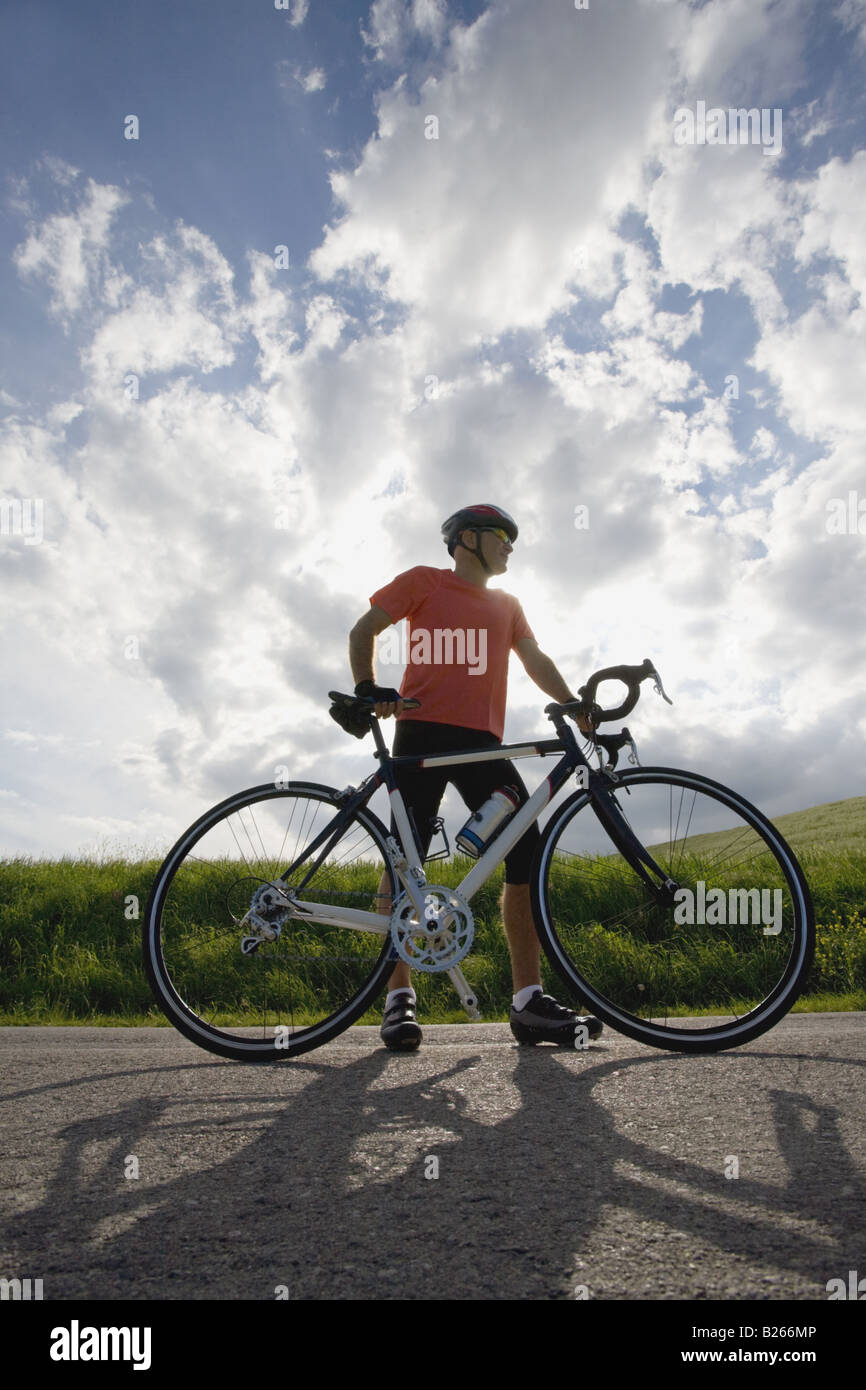 Front view of a man standing on road with bicycle Stock Photo