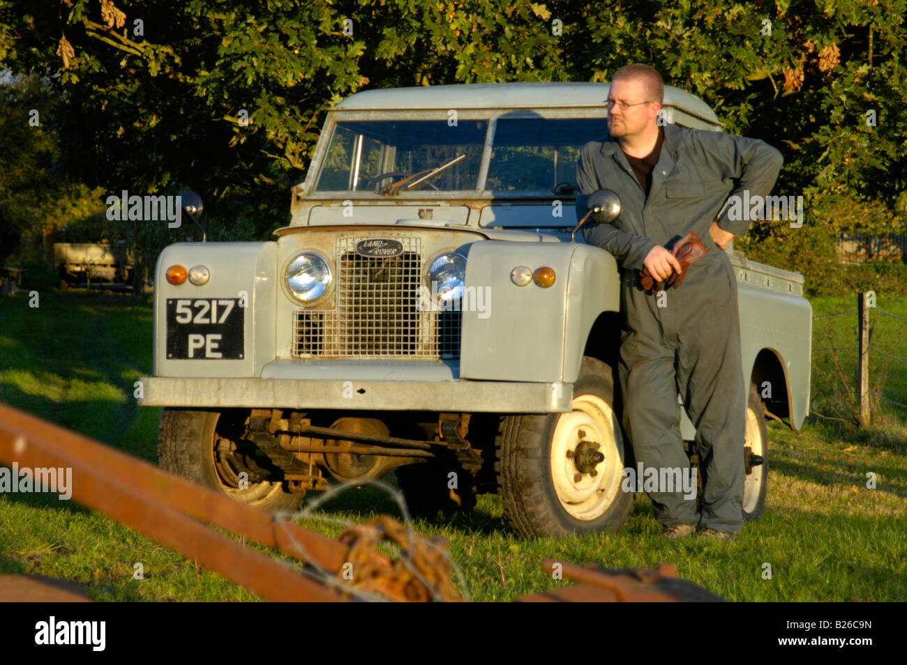 Workman in overall leaning  against a historic 1963 Landrover Series 2a truckcab in very original and full working - Stock Image