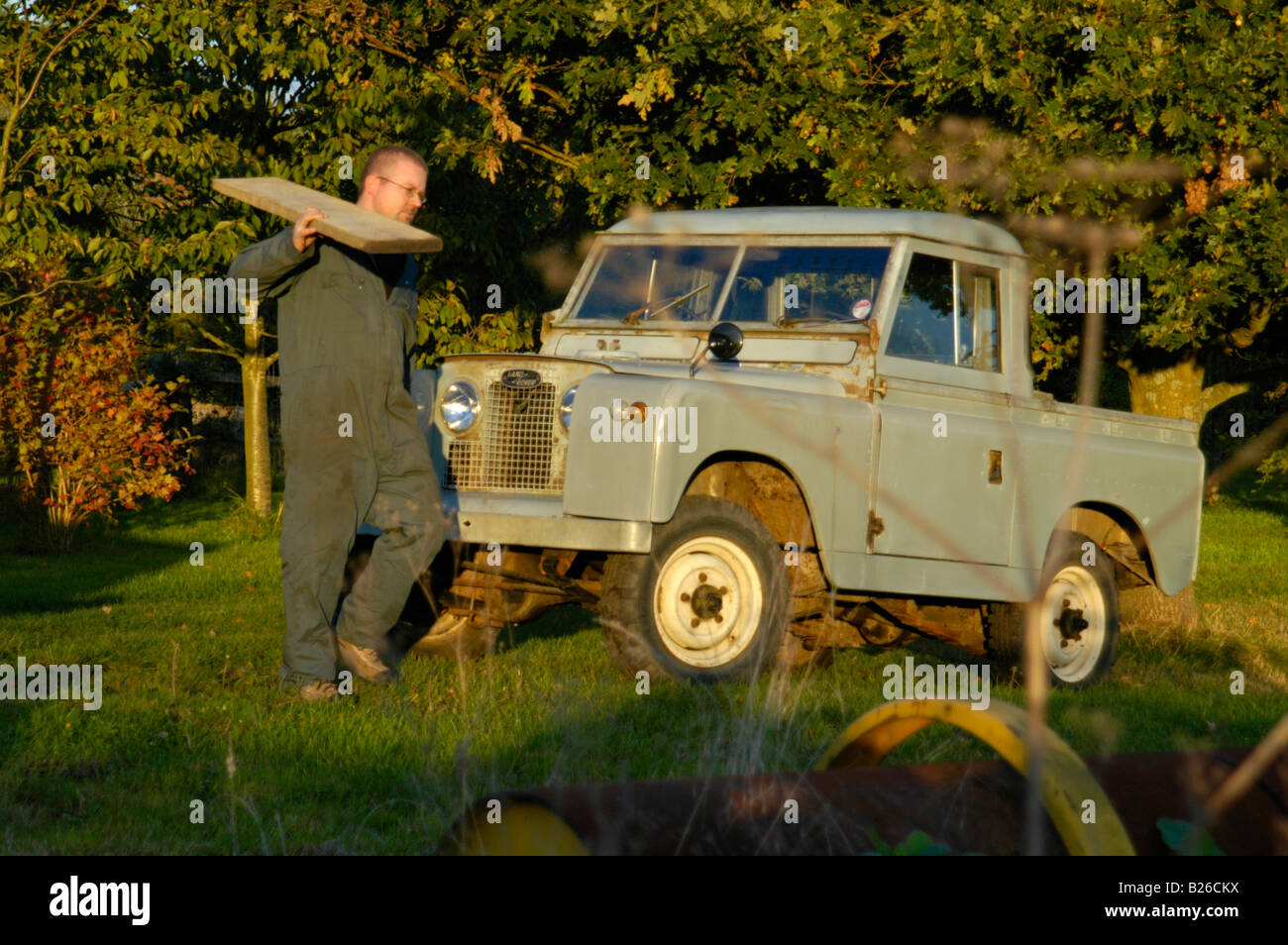 Workman loading a timber beam into a historic 1963 Landrover Series 2a truckcab in original and full working condition. - Stock Image