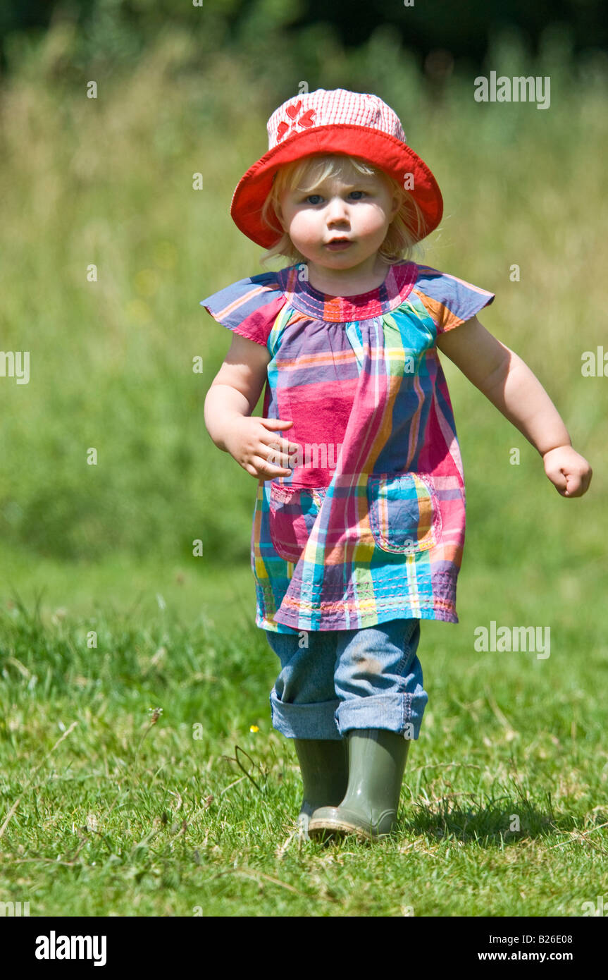 A cute young girl toddler running walking wearing wellies and a red sun hat  on a sunny day in a green field. 5ee5ffa9912c