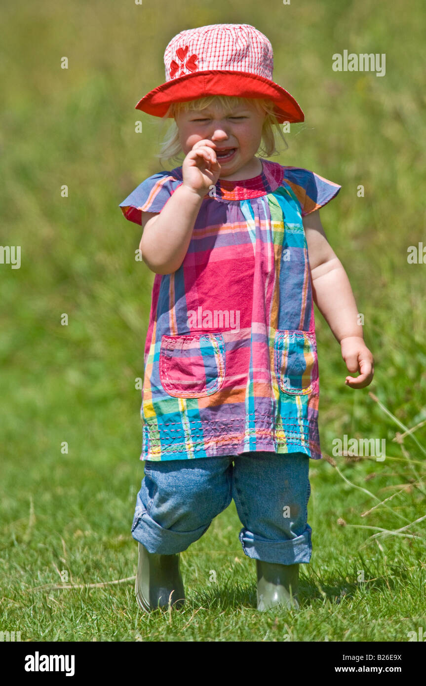 A cute young girl toddler crying wearing wellies and a red sun hat on a  sunny 8bb589a2b6b8