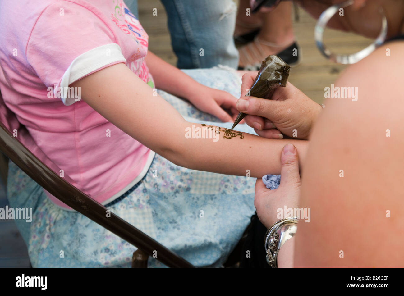 Young girl having henna tattoo on fore arm - Stock Image