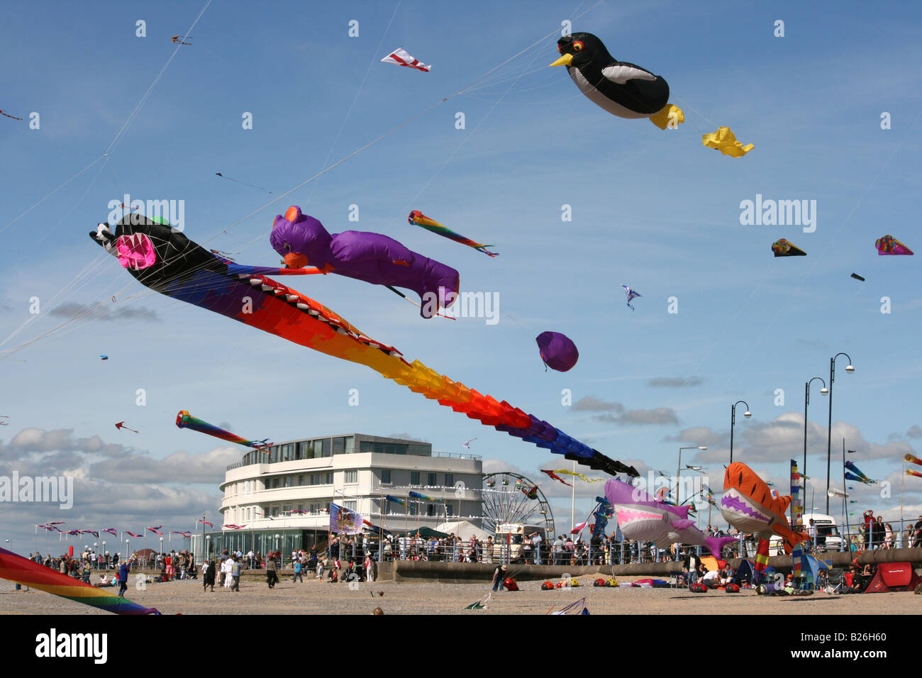 View from the beach to Morecambe Promenade and Midland Hotel during the Catch the Wind Kite Festival. - Stock Image