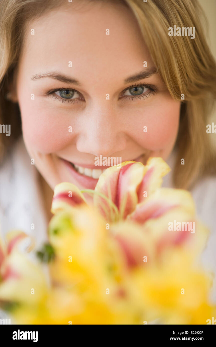 Woman smelling flower - Stock Image