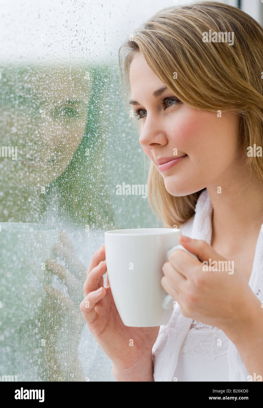 Woman looking out rainy window - Stock Image