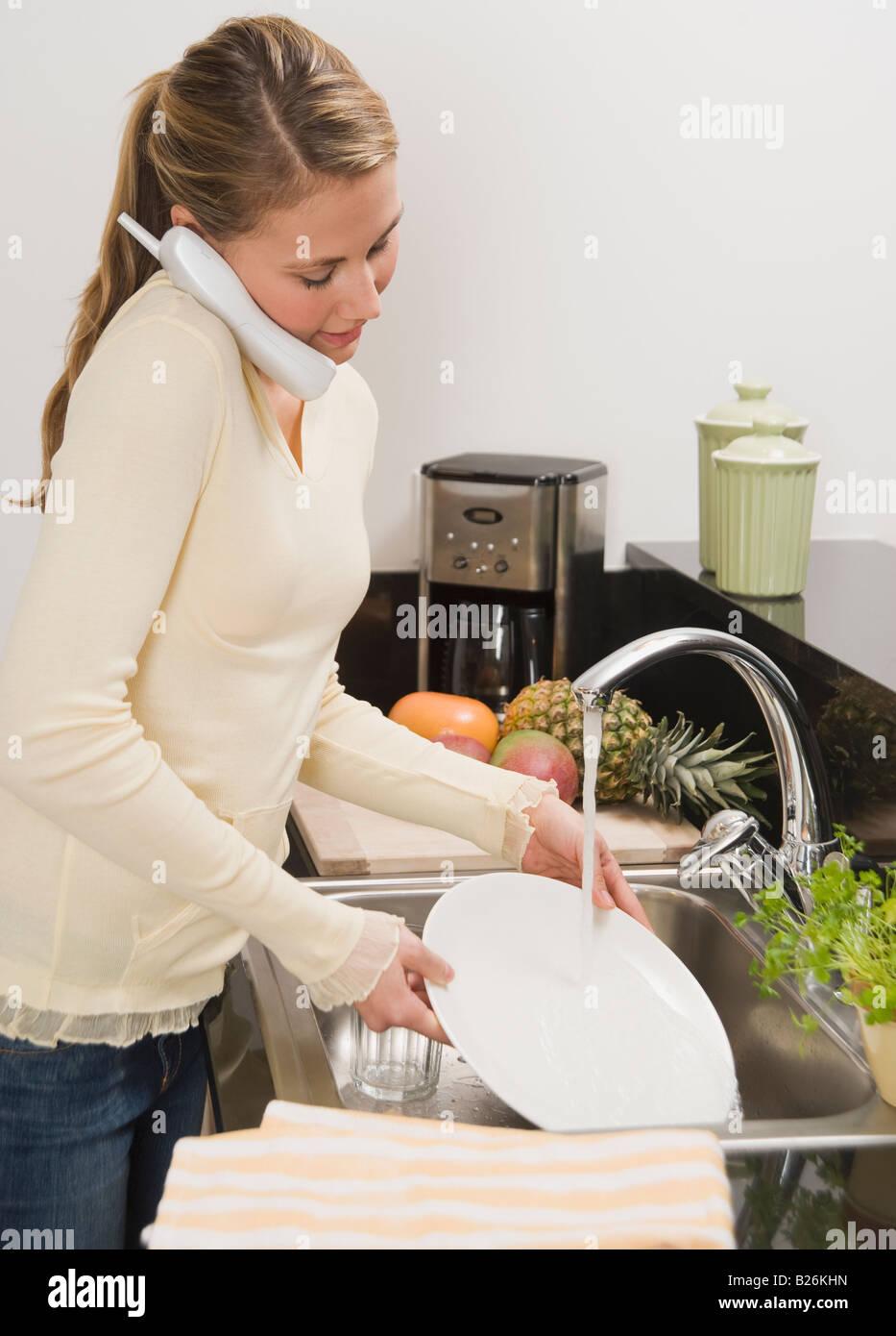 Woman washing dishes - Stock Image