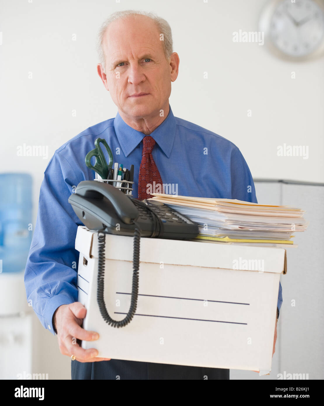 Senior businessman carrying box of office items Stock Photo
