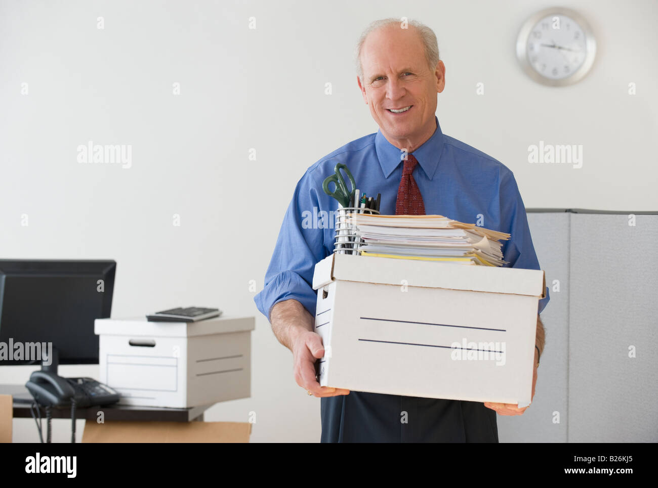 Senior businessman carrying box and office supplies - Stock Image