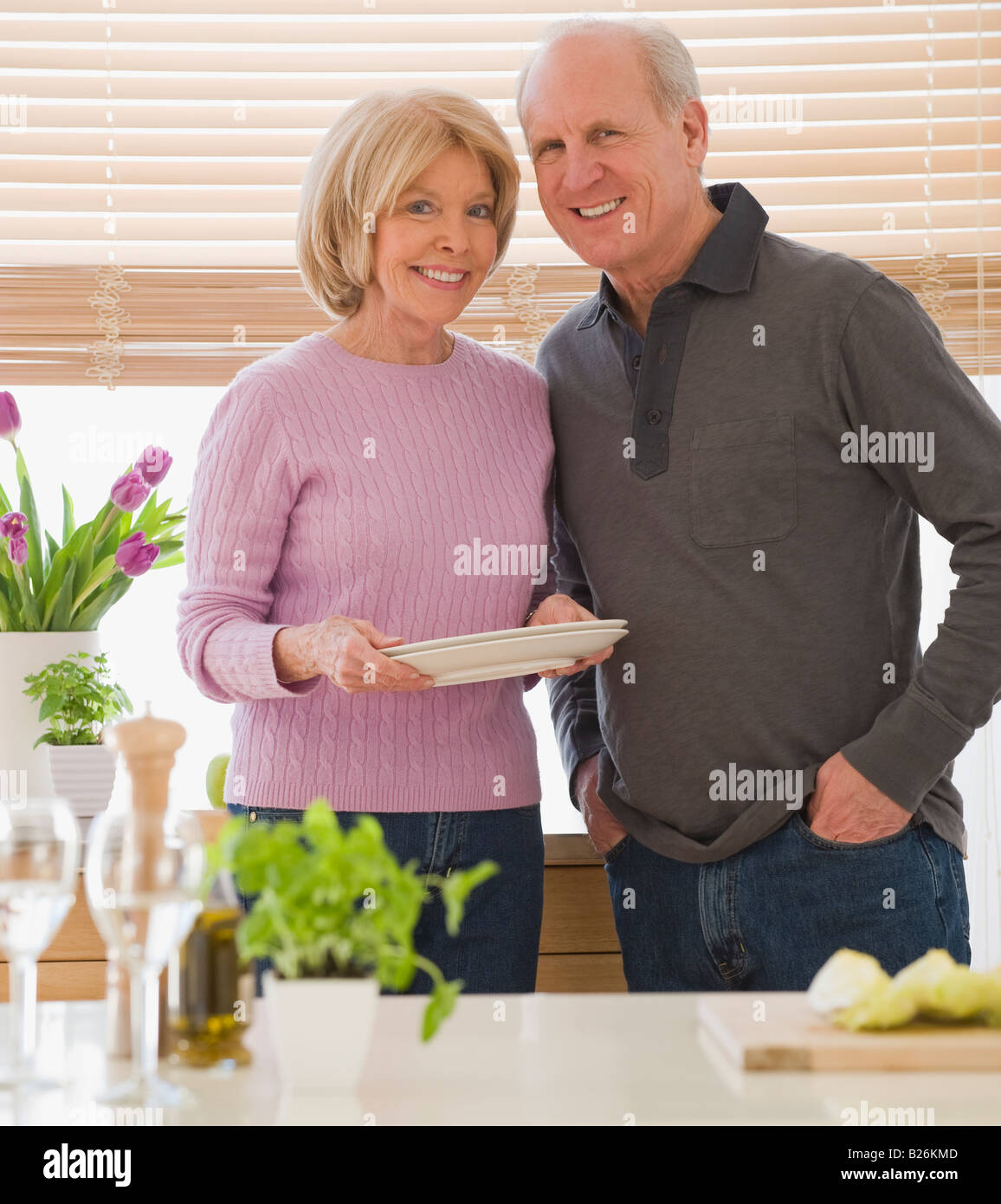 Senior couple with dishes in kitchen - Stock Image