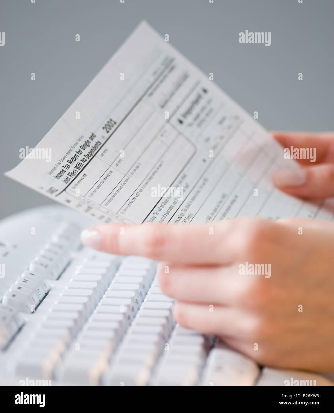 Woman holding tax form over keyboard - Stock Image