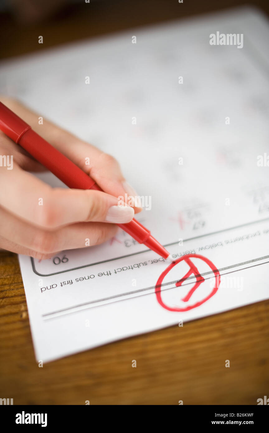 Teacher writing F grade on worksheet - Stock Image