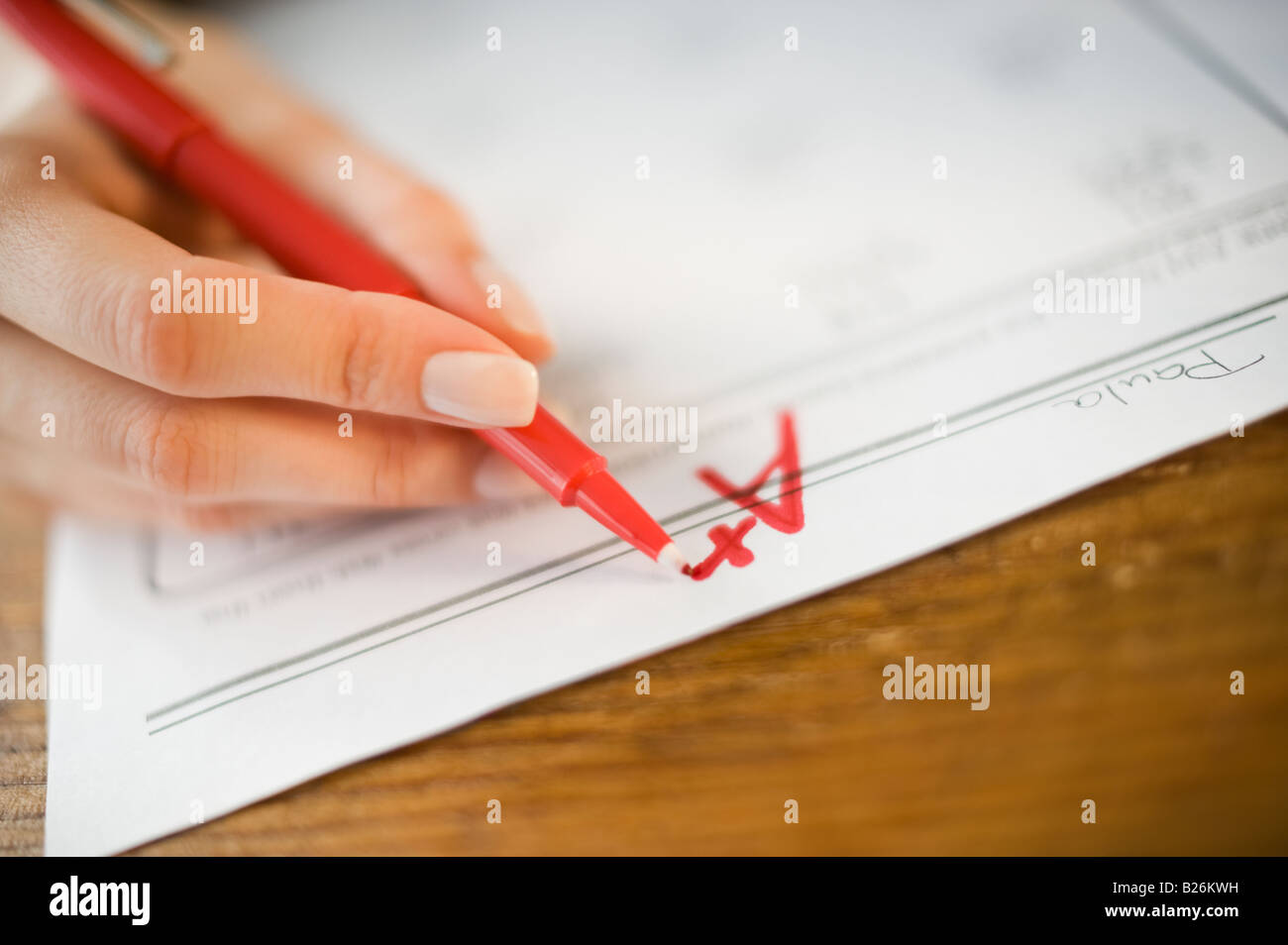 Teacher writing A plus grade on worksheet - Stock Image