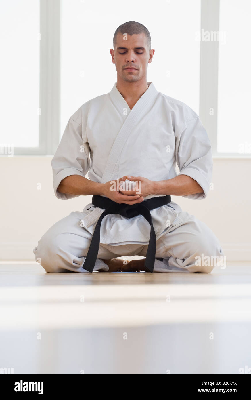 Hispanic male karate black belt meditating - Stock Image
