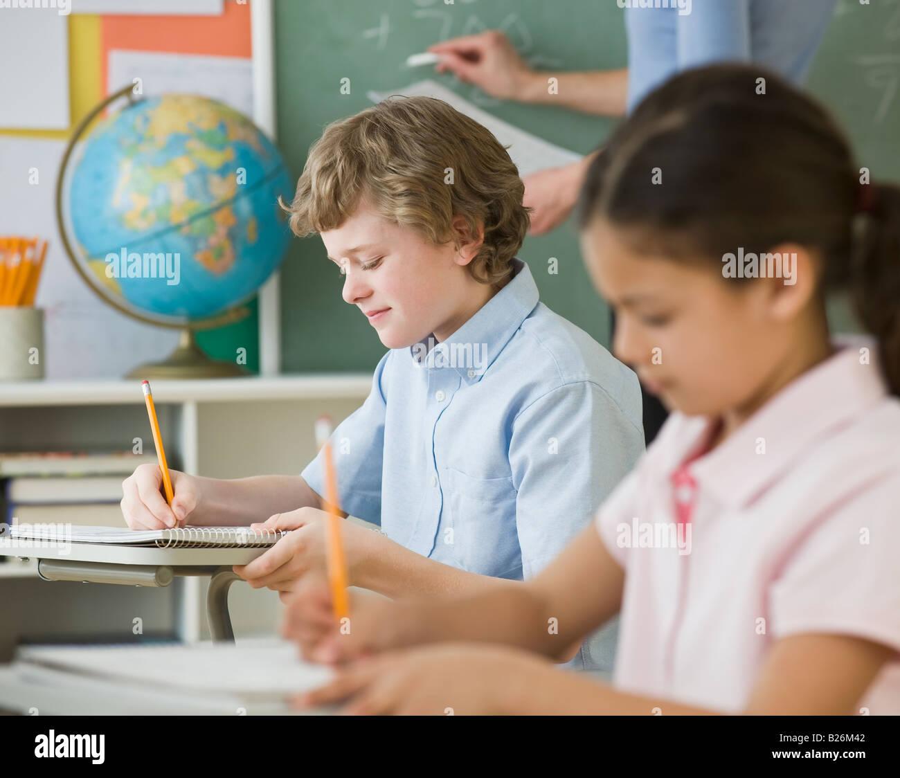 Multi-ethnic children writing at school desks - Stock Image