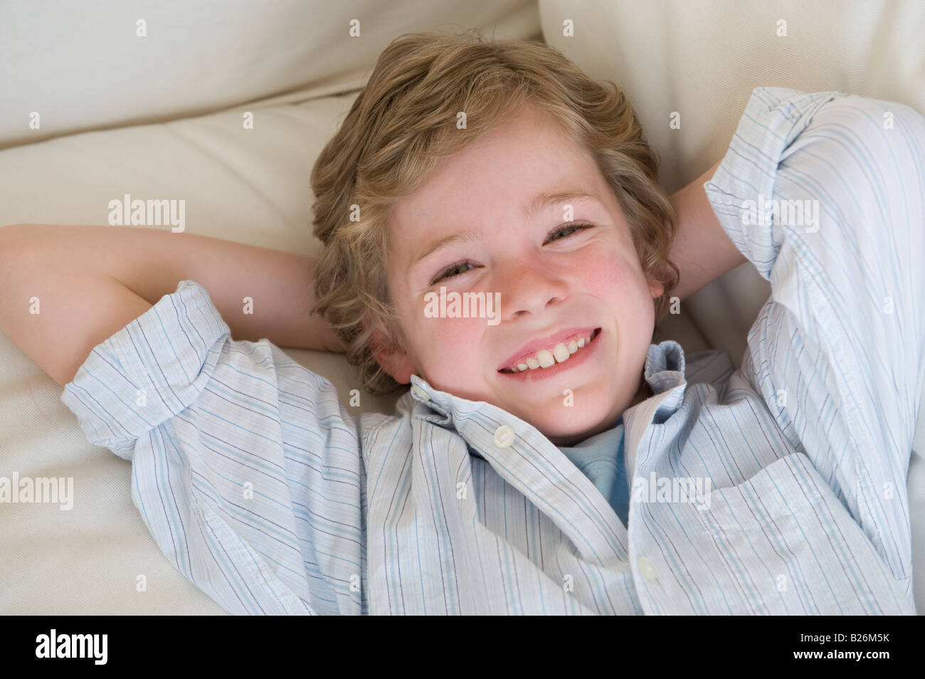 Boy laying on sofa - Stock Image