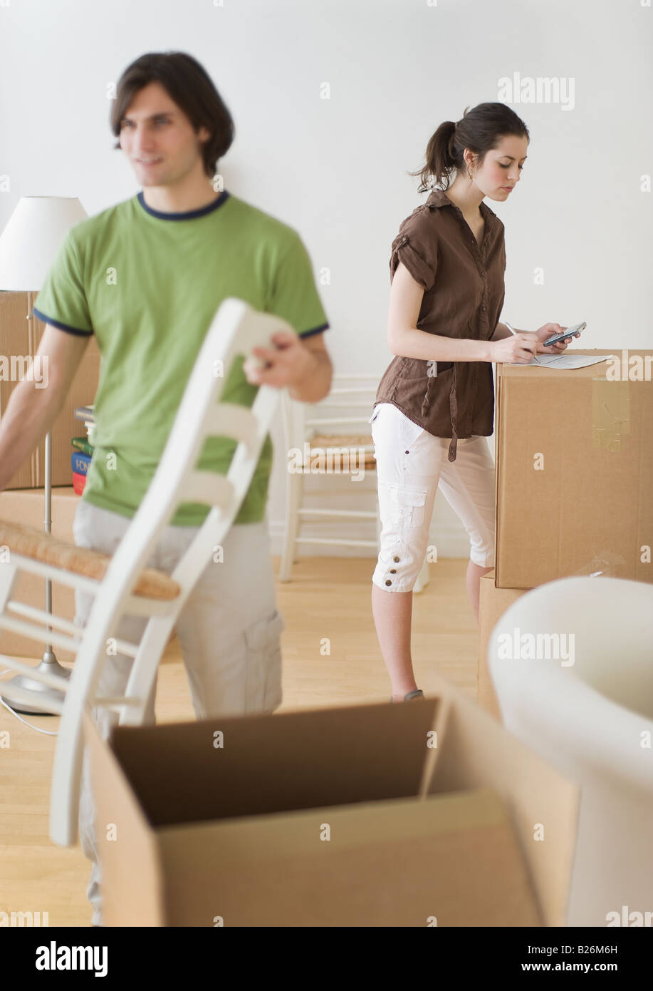 Couple and moving boxes in new home - Stock Image