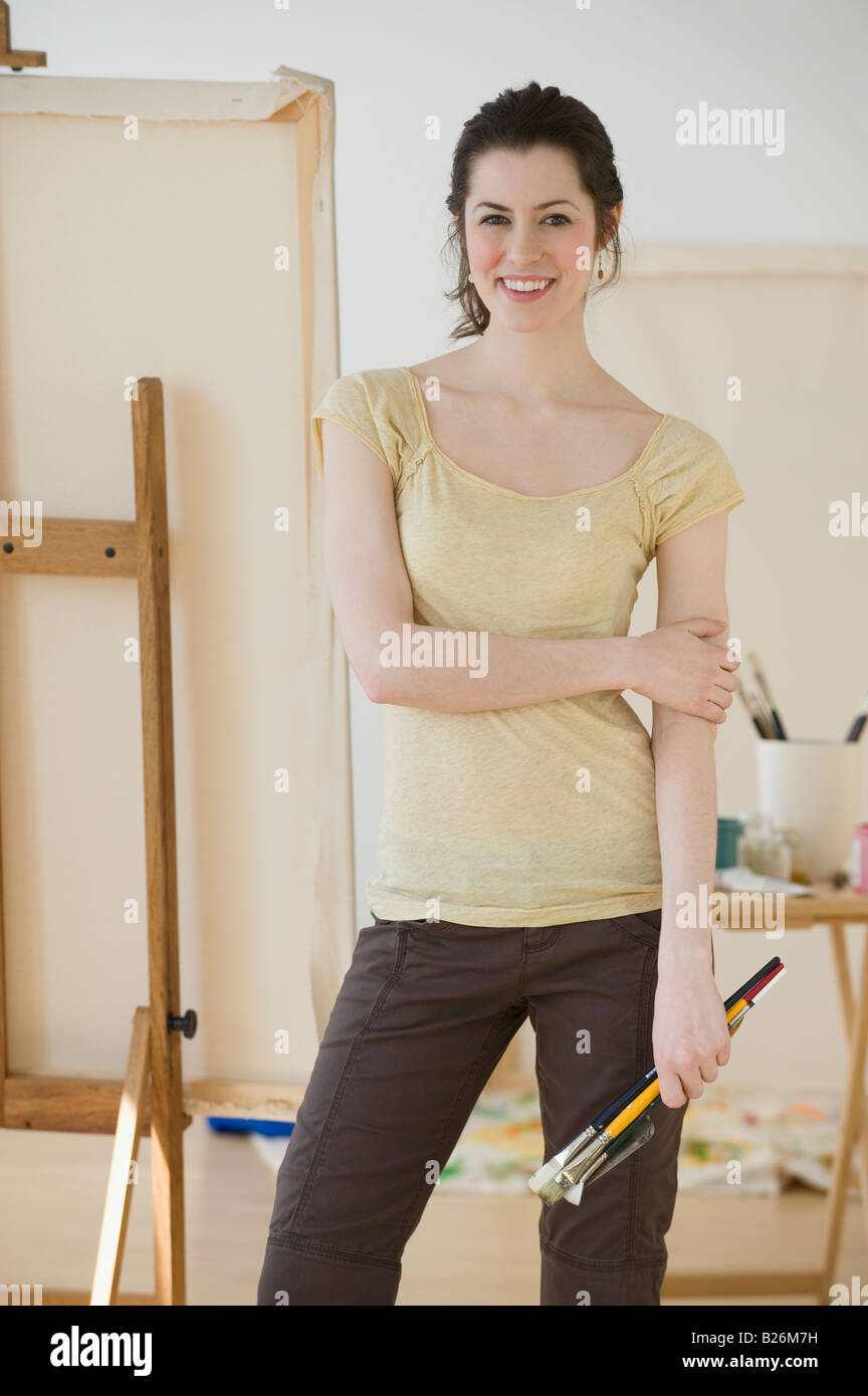 Woman holding paintbrushes in front of easel Stock Photo
