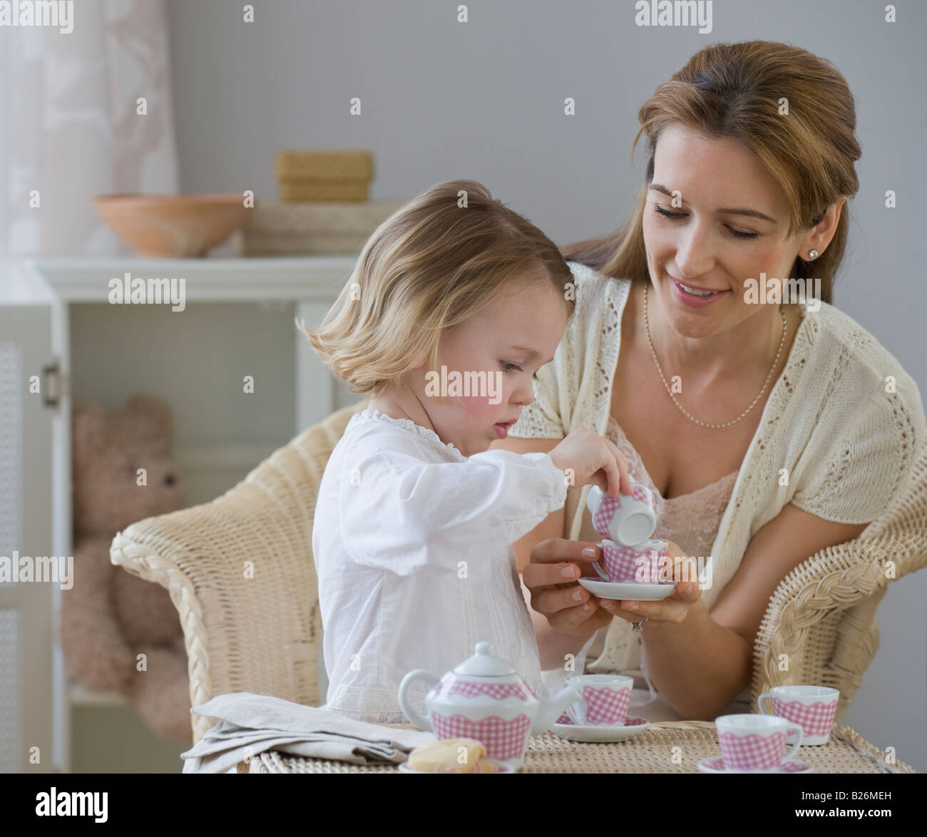 Mother and daughter playing with tea set - Stock Image