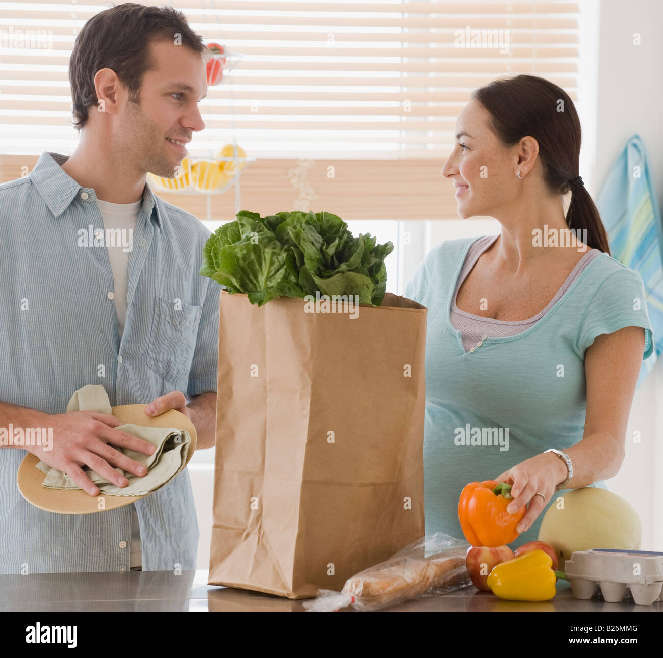 Pregnant Hispanic couple unpacking groceries - Stock Image