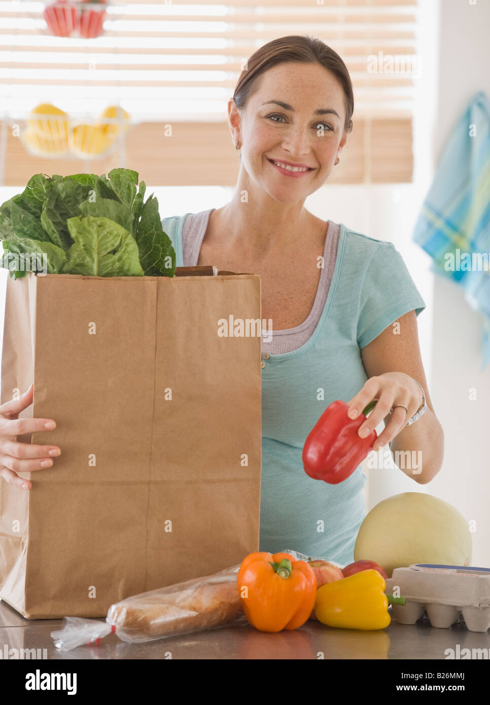 Pregnant Hispanic woman unpacking groceries - Stock Image