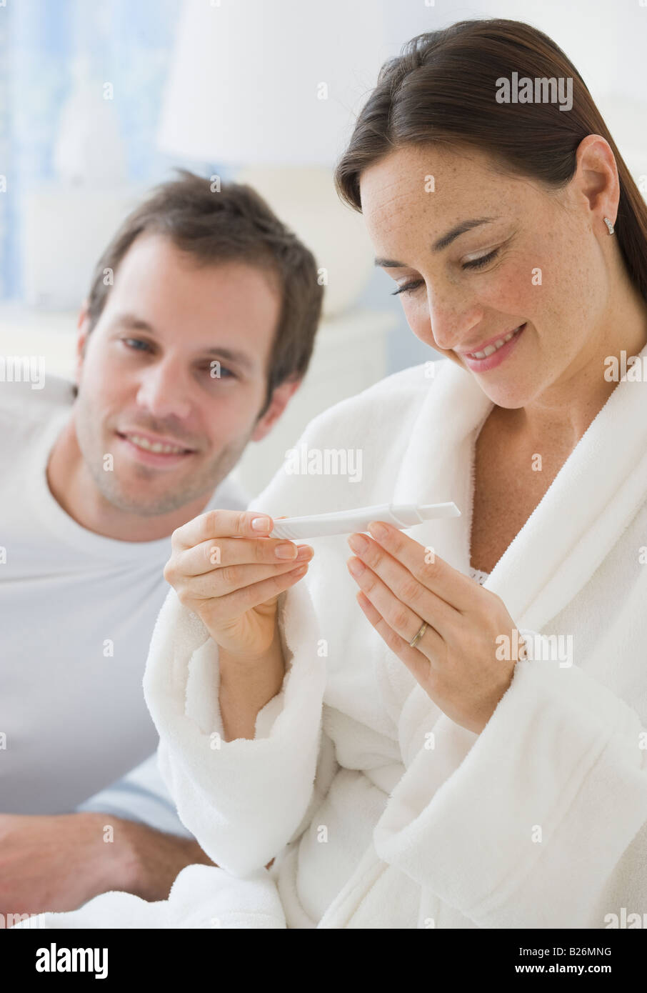 Hispanic couple looking at pregnancy test - Stock Image