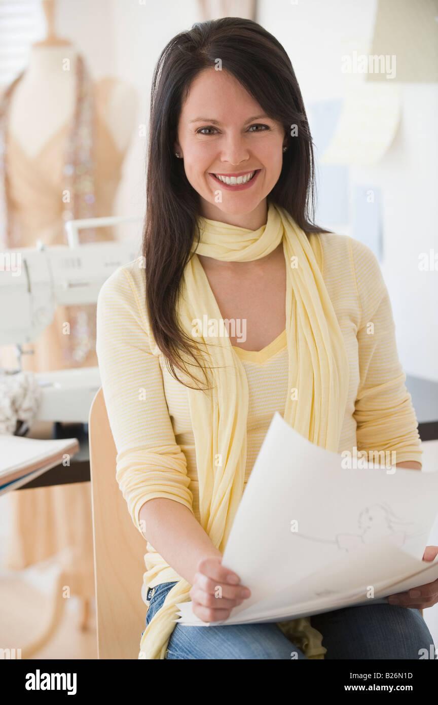 Female clothing designer holding drawings - Stock Image