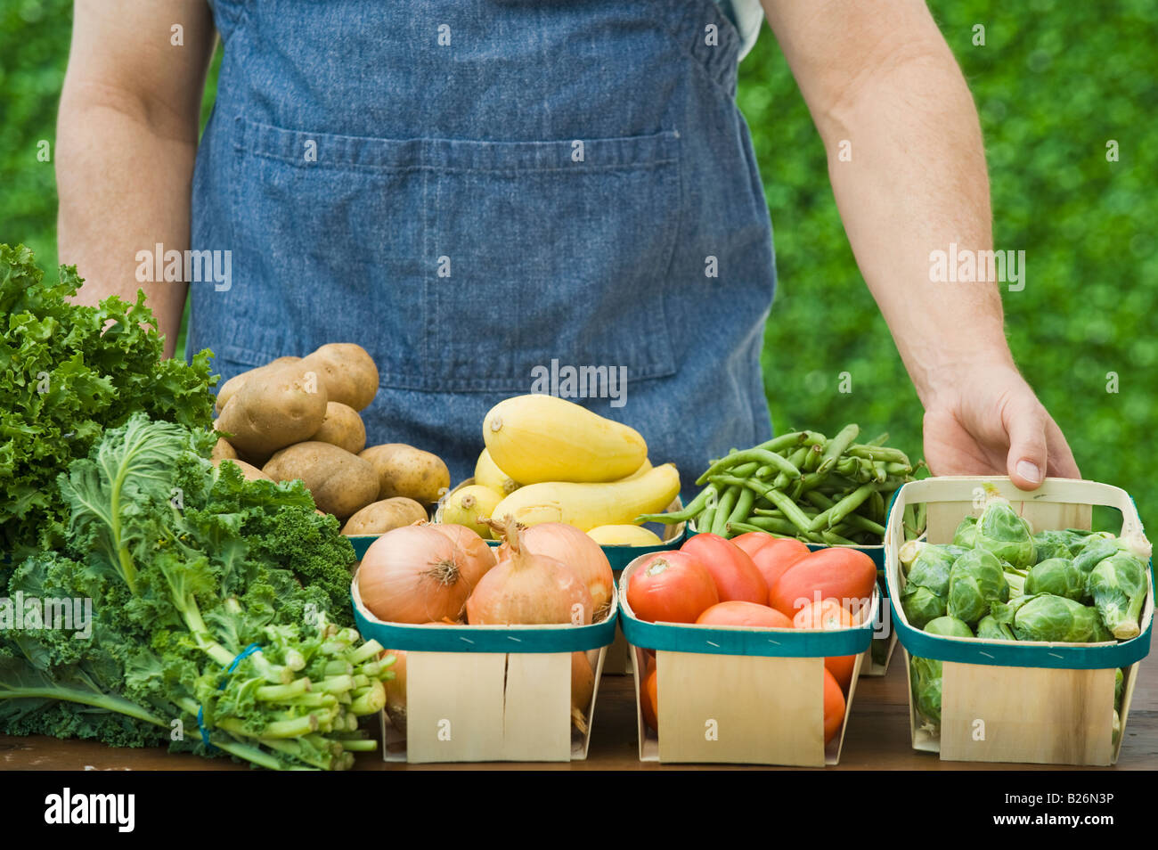 Farmer next to baskets of vegetables - Stock Image