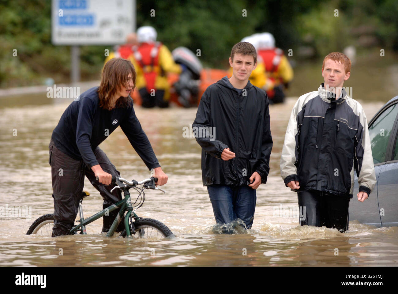 THREE BOYS WADE THROUGH FLOODWATER IN TEWKESBURY DURING THE FLOODS IN GLOUCESTERSHIRE JULY 2007 UK - Stock Image