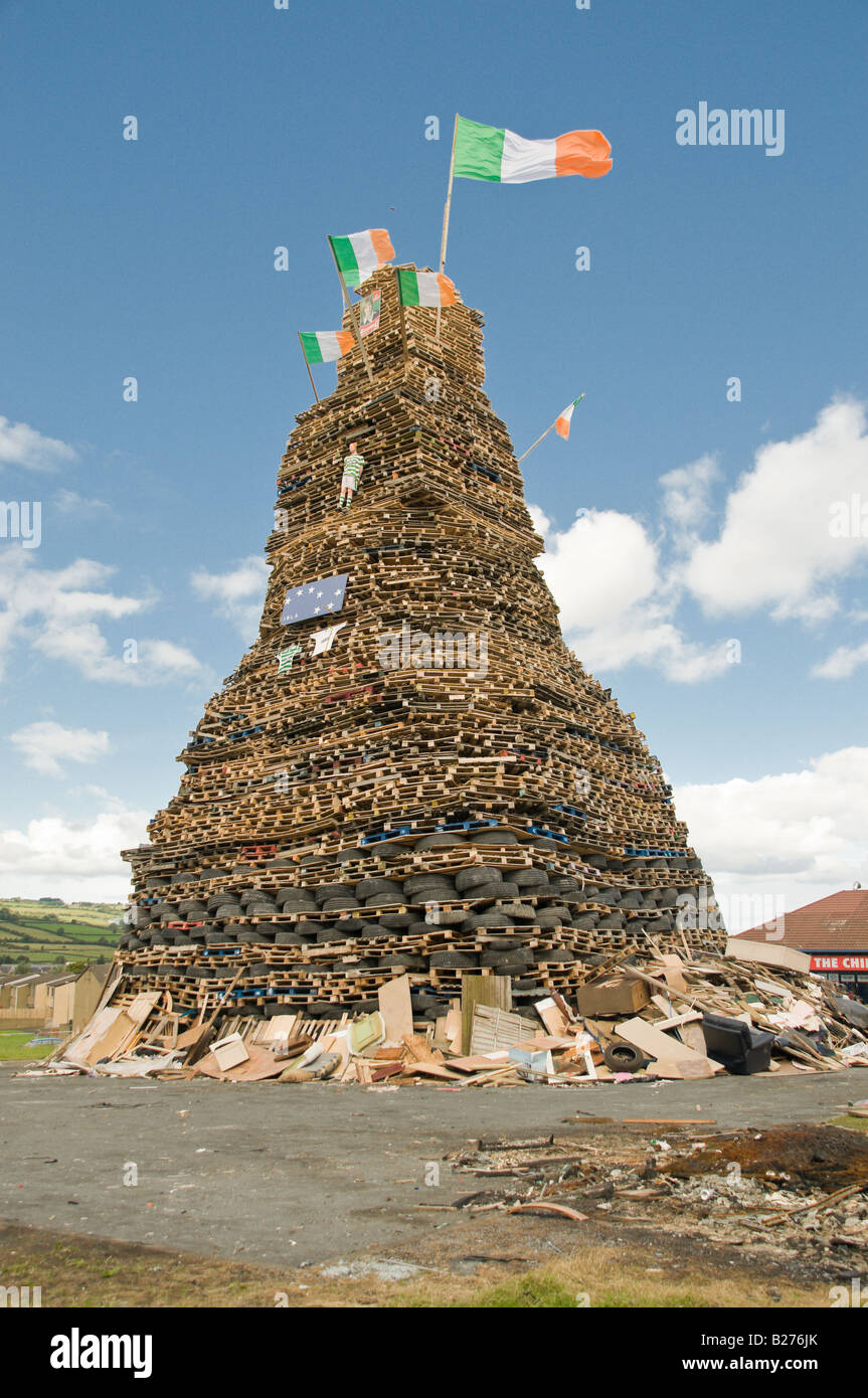 Large bonfire in Mossley, Newtownabbey, Northern Ireland, with Irish Tricolour flags and Celtic shirts - Stock Image
