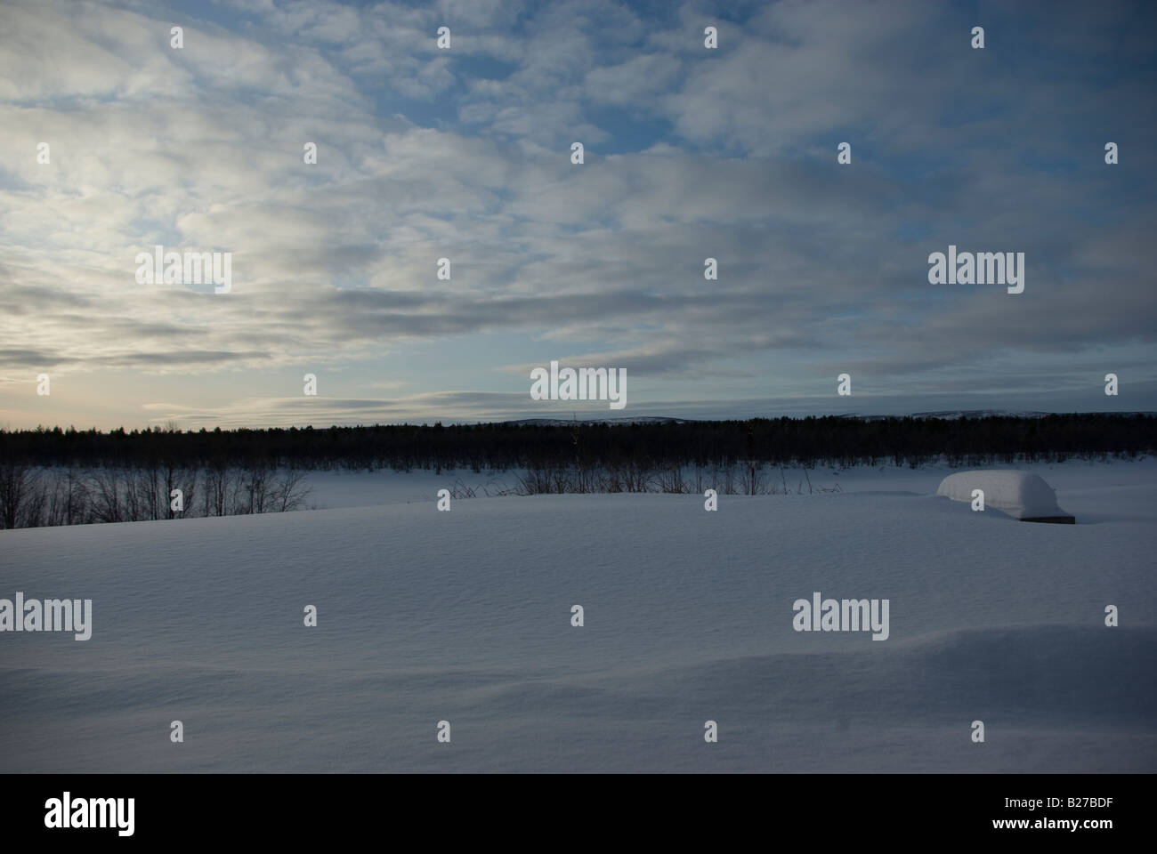 A bench covered in snow, with Tornio river and fells on Sweden's side of the river in the background - Stock Image