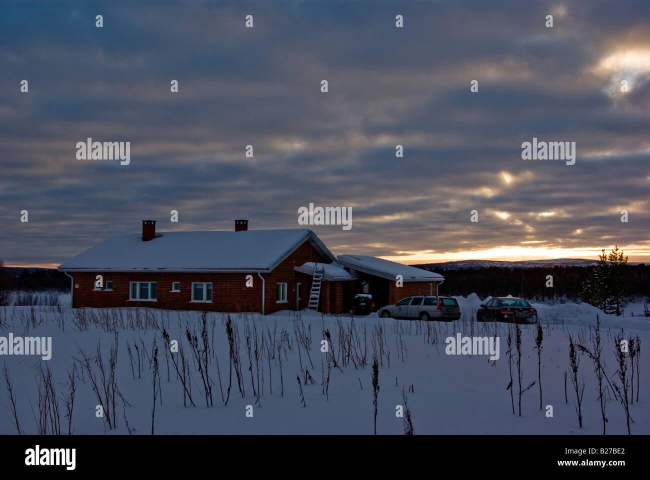 A red brick house covered in snow with three cars parked in front in the Finnish Lapland - Stock Image
