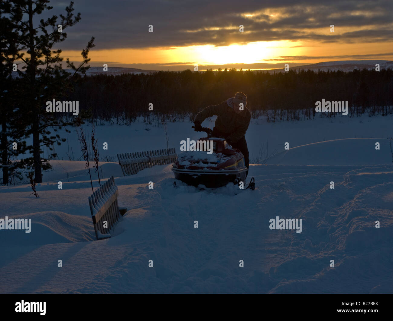 Snow mobile returns from trip with the sun setting behind the fells on the swedish side of Tornio river - Stock Image