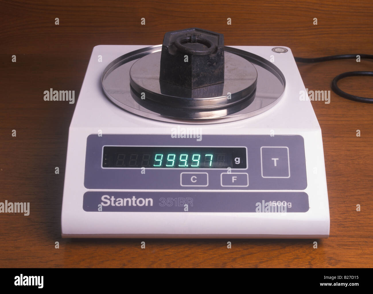 weighing a 1kg mass on a top pan balance - Stock Image