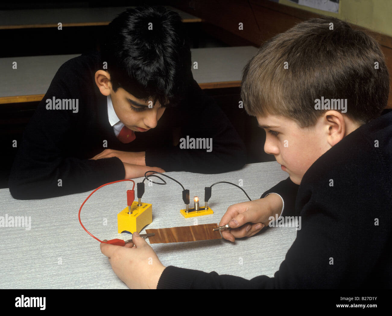 boys testing electrical conductivity of copper - Stock Image